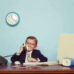 Young Boy Businessman Talks on the Telephone
